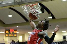 Justin Hill (11) of Travis makes a slam-dunk during the fourth quarter of a Boys 6A Region III Bi-District play-off game between the Mayde Creek Rams and the Travis Tigers on Tuesday, February 25, 2020 at Coleman Coliseum, Houston, TX.