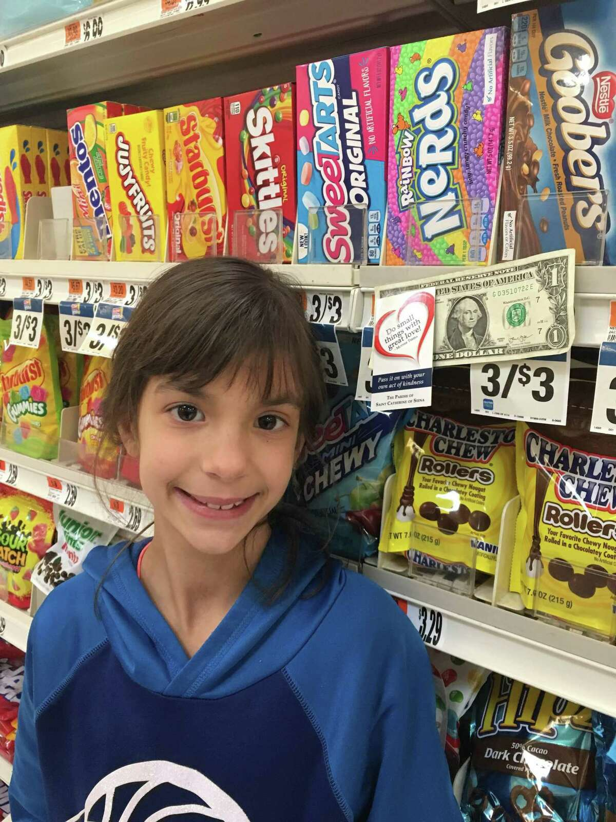 St. Catherine of Siena School 7th grader Siena, leaves $1 in the candy aisle at Stop & Shop with the intention that it brightens someone's day.