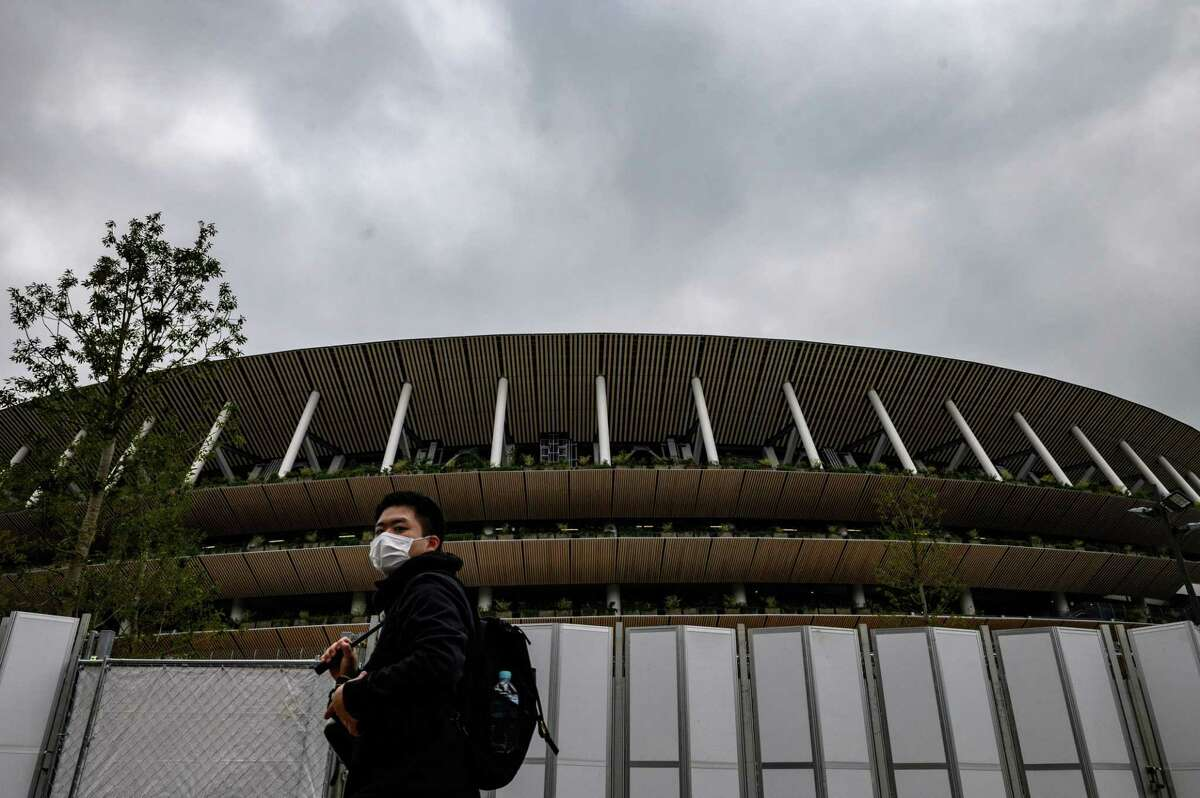 A man wearing a face mask, amid concerns over the spread of the COVID-19 novel coronavirus, walks past the National Stadium in Tokyo on February 26, 2020. NBC Sports Group said it is moving ahead with its plans to broadcast the summer Olympics in Tokyo, which are scheduled to run from July 24 to Aug. 9, 2020.
