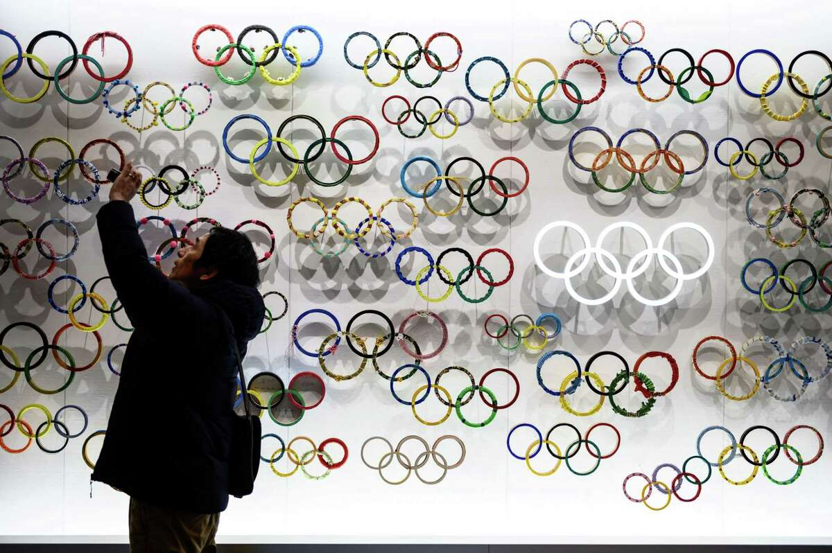 TOPSHOT - A man takes pictures at the Japan Olympic Museum in Tokyo on February 26, 2020. (Photo by Philip FONG / AFP) (Photo by PHILIP FONG/AFP via Getty Images)