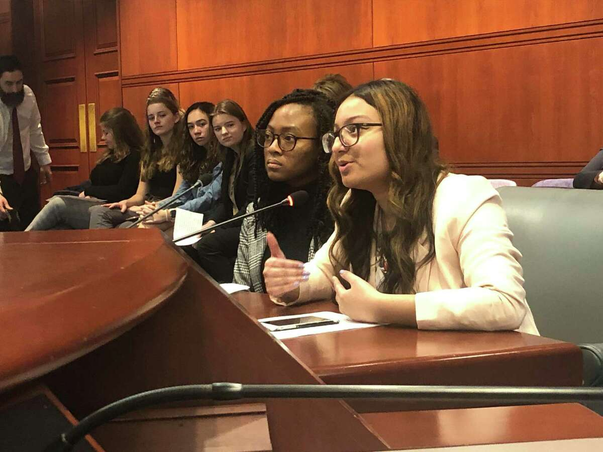 Mariam Khan, right, a Hamden High School senior and lead organizer of the Connecticut chapter of PERIOD, a national advocacy group pushing menstrual equity, testifies before the legislature's Public Health Committee in support of a bill that would require schools provide free feminine hygiene products in middle and high schools across the state.