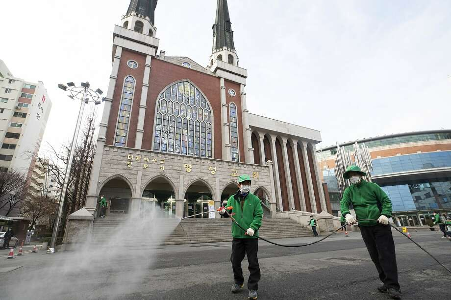 Workers wearing face masks spray disinfectant in front of a church as a precaution in Seoul. Photo: Yun Dong-jin / Yonhap