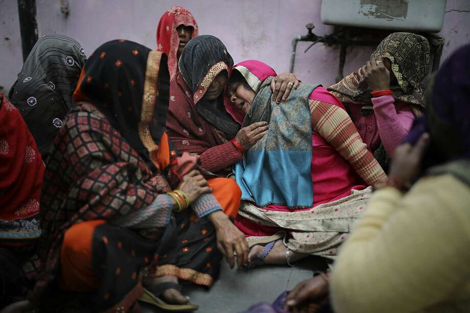 Family members of Rahul Solanki, who was killed during clashes between Hindu mobs and Muslims protesting a contentious new citizenship law, weep outside a mortuary in New Delhi. Photo: Altaf Qadri / Associated Press