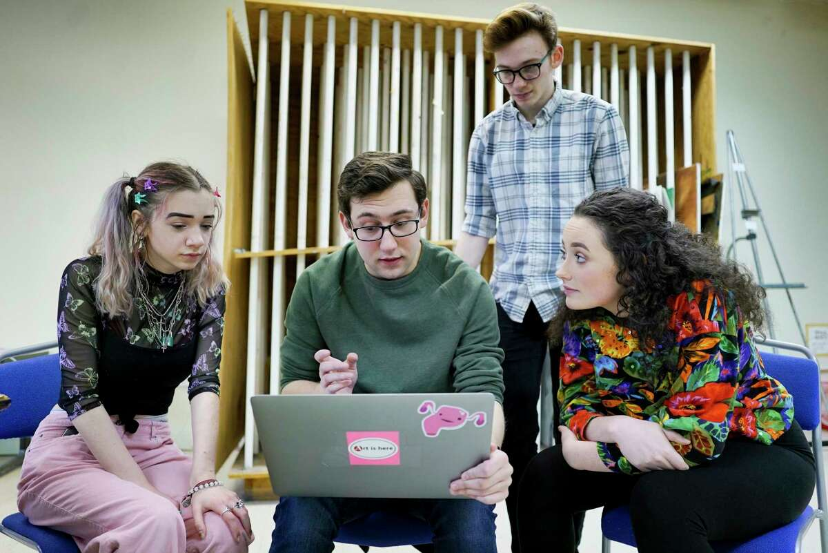 Questar III students, cinematographer Emma Rinaldi, left, from Troy High School, writer and director Jon Maltz, second from left, from Shenendehowa High School, actor Matthew Joseph, third from left, from Shenendehowa High School, and actor Claire Flynn, from Averill Park High School, look over footage from a PSA on teen suicide prevention that the group filmed earlier on Wednesday, Feb. 26, 2020, in Troy, N.Y. The teens are working with the Rensselaer County Suicide Prevention Task Force to create the PSA. (Paul Buckowski/Times Union)