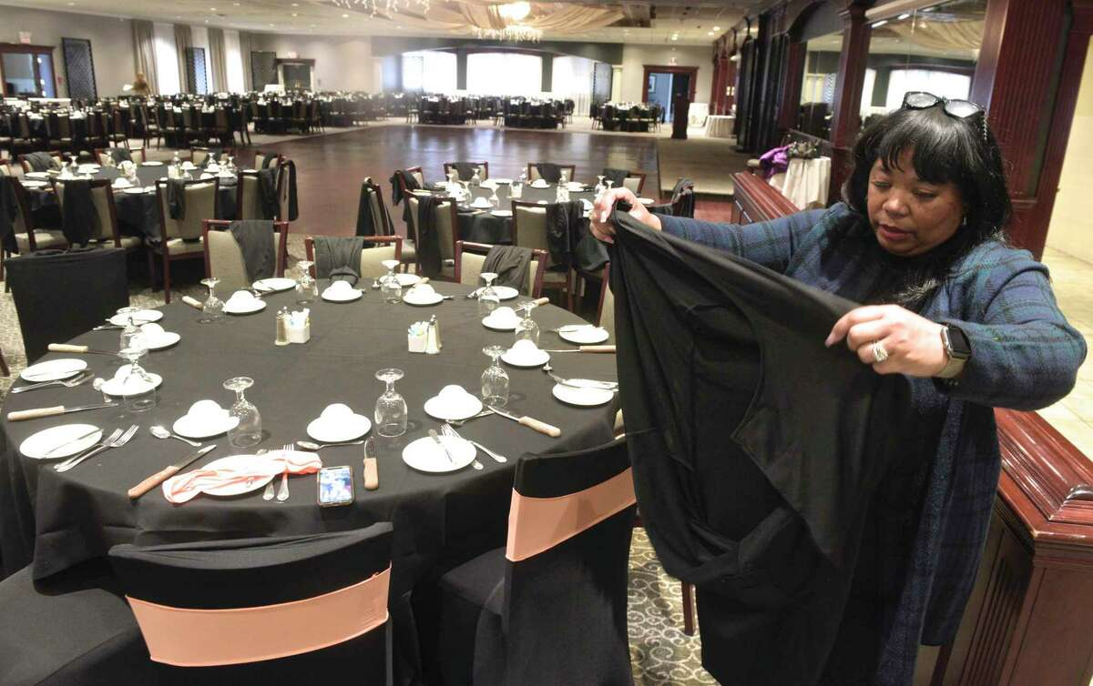 Karen Wright, gala chair, works at putting on a chair cover as the Hord Foundation prepares for its 27th annual gala, at the Amber Room Colonnade in Danbury, Conn, on Wednesday, February 26, 2020.