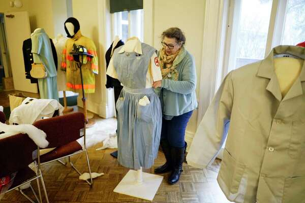 Debora Jackson, textile conservator, volunteers her time as he works with an American Red Cross uniform from the WW II era at the Hart Cluett Museum on Wednesday, Feb. 26, 2020, in Troy, N.Y. The uniforms will be part of The Way We Work(ed) exhibit. The Hart Cluett Museum is one of 10 small museums across the country participating in a new program with the Smithsonian Institute using pieces from the local collections to localize a national exhibit. (Paul Buckowski/Times Union)