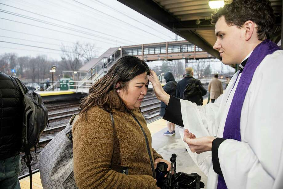 Derek Stefanovsky, Assistant Rector at St. Luke's Church, offers 'Ashes to Go' to commuters at Noroton's train station on Ash Wednesday, Feb. 26, 2020. Photo: Bryan Haeffele / Hearst Connecticut Media / Hearst Connecticut Media