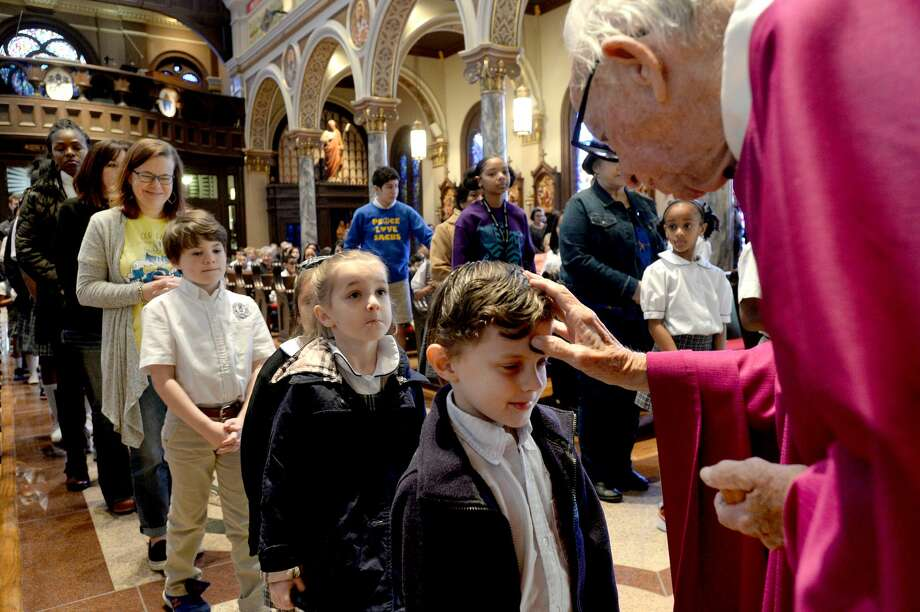 Msgr. Jack Dinkins distributes ashes during Ash Wednesday mass at St. Anthony Cathedral Basilica. Congregants and students from St. Anthony School filled the basilica for the early morning mass to begin the season of Lent. Photo taken Wednesday, February 26, 2020 Kim Brent/The Enterprise Photo: Kim Brent/The Enterprise