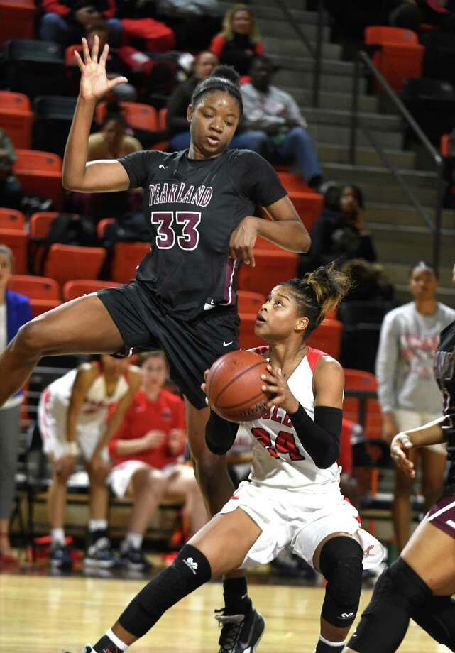 """Atascocita senior guard DeDe Davis, right, finds her lane to the hoop blocked by Pearland 6'3"""" senior center De Gaston (33) during the 4th quarter of their UIL Girls' Basketball Region III Conference 6A Area Playoff matchup at LaPorte High School on Feb. 21, 2020. Photo: Jerry Baker, Houston Chronicle / Contributor / Houston Chronicle"""