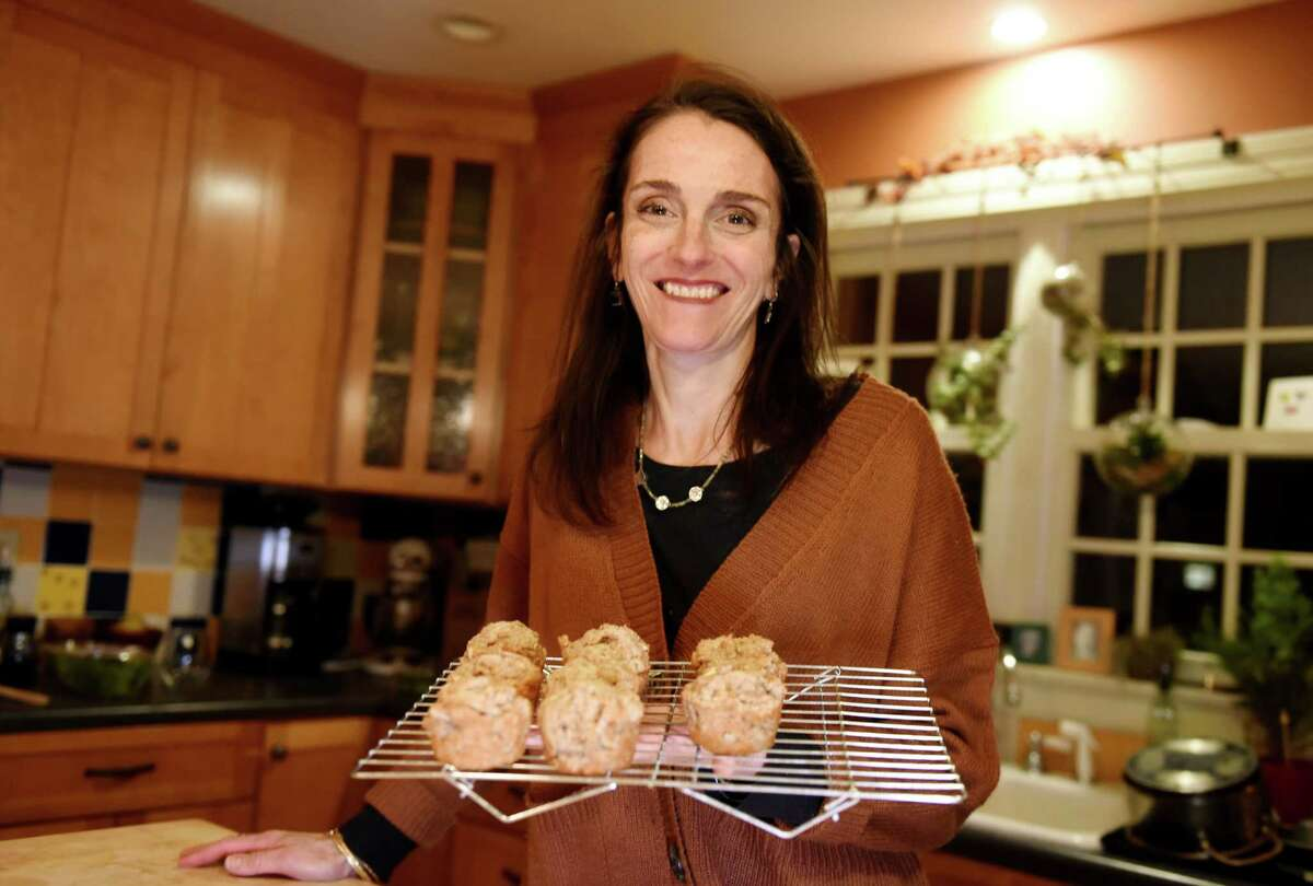 Caroline Barrett holds a tray of her spice cake apple muffins on Wednesday, Feb.19, 2020, in Delmar, N.Y. (Will Waldron/Times Union)