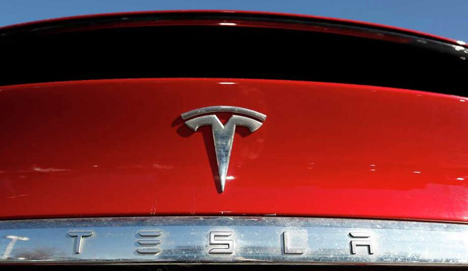 FILE - In this Feb. 2, 2020 file photograph, the company logo sits on an unsold 2020 Model X at a Tesla dealership in Littleton, Colo. Shares of Tesla Inc. fell 4% in early trading Thursday, Feb. 13, after the electric vehicle and solar panel maker said it would sell more than $2 billion worth of additional shares. The move comes just two weeks after CEO Elon Musk said the company had enough cash to fund its capital programs and it didn't need to raise any more money. (AP Photo/David Zalubowski, File) Photo: David Zalubowski / Associated Press / Copyright 2020 The Associated Press. All rights reserved.