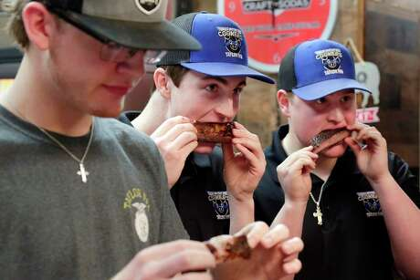 Katy students (from left) Austin Flynn, Kyle Foster and Walker Mills, from James E. Taylor High School's FFA barbecue team, known as the Teenage Mutant Ninja Cookers, sample smoked ribs prepared by pitmaster and mentor Brett Jackson at his restaurant, Brett's Barbecue Shop.