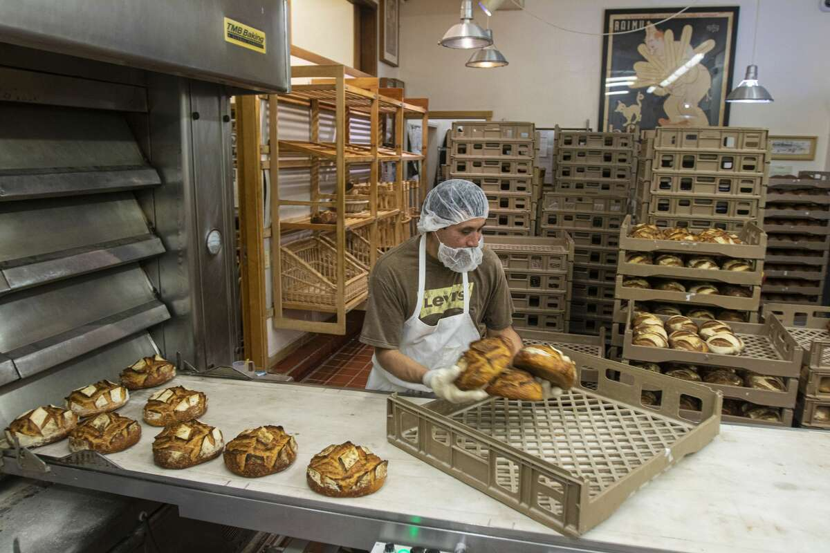 Armando Castillo takes bread out of the oven during an evening shift at Acme Bread Company in Berkeley, Calif., Tuesday, Feb. 25, 2020.