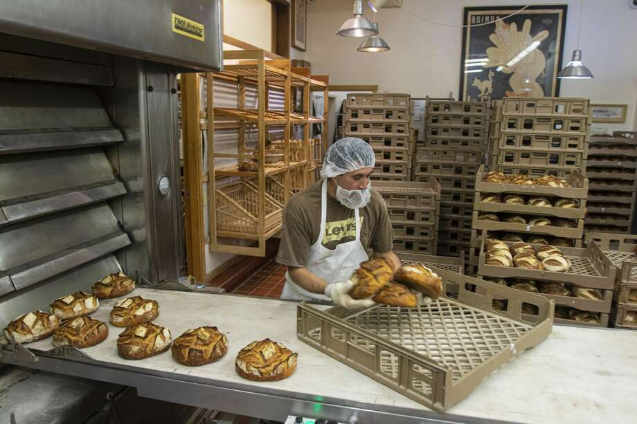 Armando Castillo takes bread out of the oven during an evening shift at Acme Bread Company in Berkeley, Calif., Tuesday, Feb. 25, 2020. Photo: Chris Preovolos