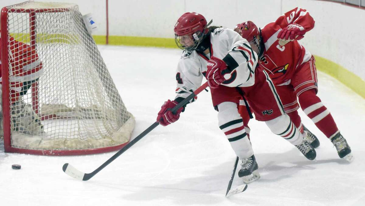 New Canaan's Kaleigh Harden (4) sends the puck out from behind the net during a girls ice hockey game against Greenwich at the Darien Ice House on Jan. 9, 2020.