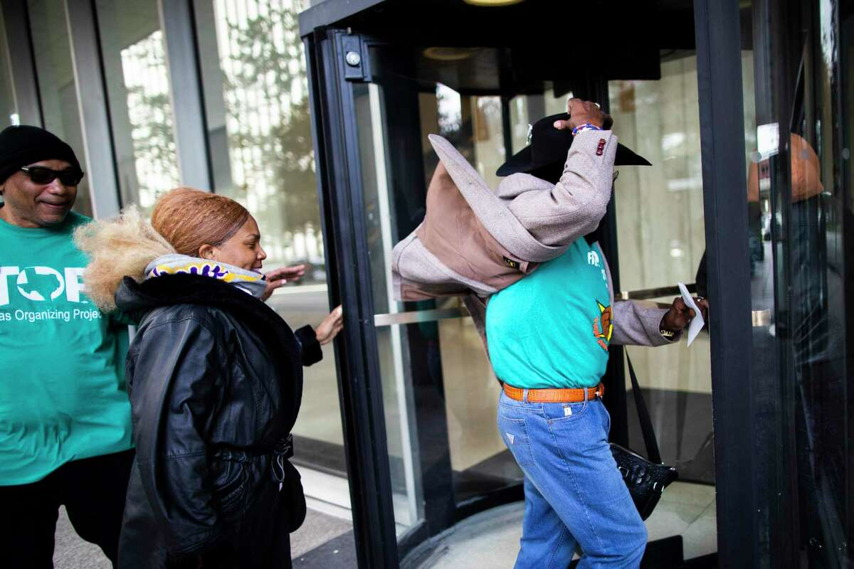 Members of the Texas Organizing Project and allies enter the building of the Harris County Office of District Attorney to try to hand a letter to the district attorney Kim Ogg on Wednesday, Feb. 26, 2020, in Houston.