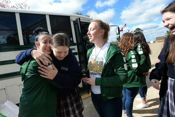 Team manager Ryanne Deckard laughs and hugs Jordan Morgan as sister Jodi Deckard looks on before the Legacy Lady Warriors board the bus amid a spirited school sendoff before heading to Waco for the state championship. Photo taken Wednesday, February 26, 2020 Kim Brent/The Enterprise