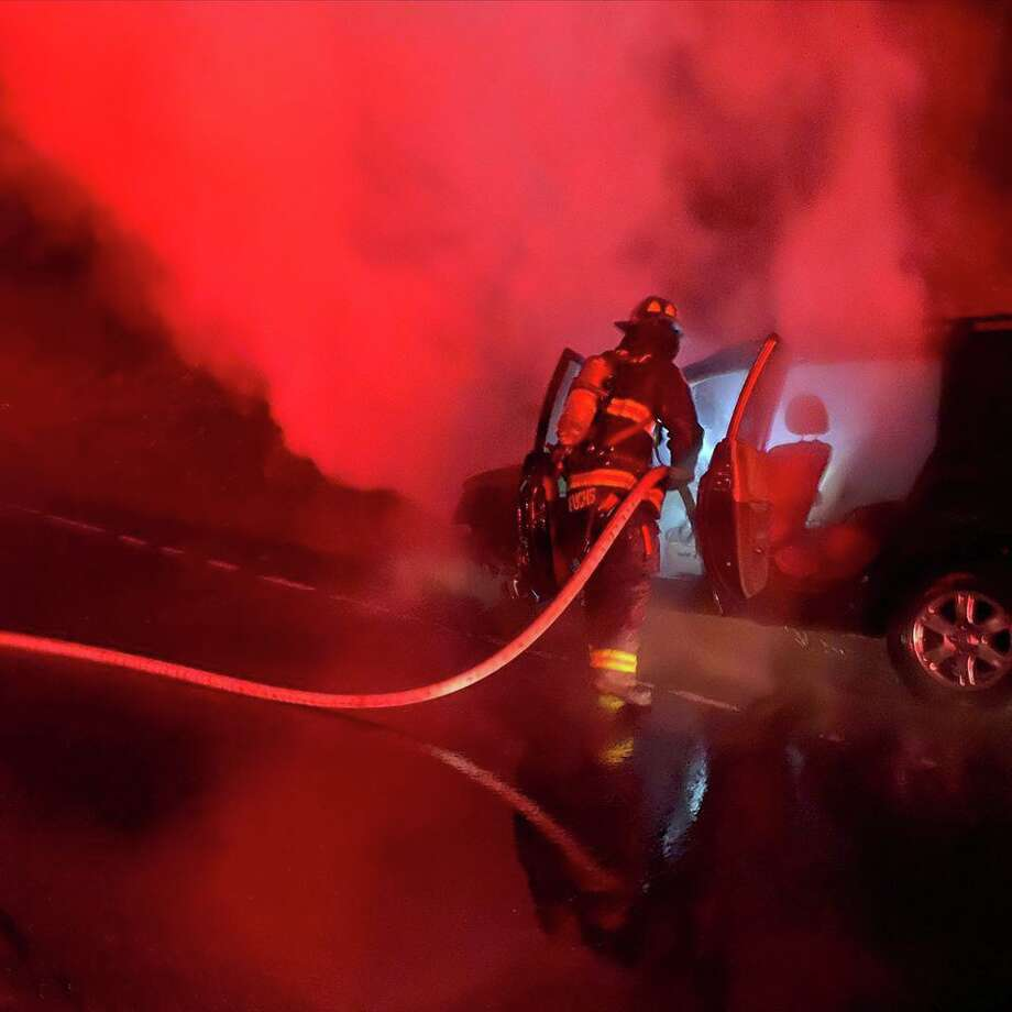 Firefighters extinguish a car fire on the Merritt Parkway in Westport, Conn., on Wednesday, Feb. 26, 2020. Photo: Contributed Photo / Westport Fire Department