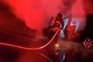 Firefighters extinguish a car fire on the Merritt Parkway in Westport, Conn., on Wednesday, Feb. 26, 2020.