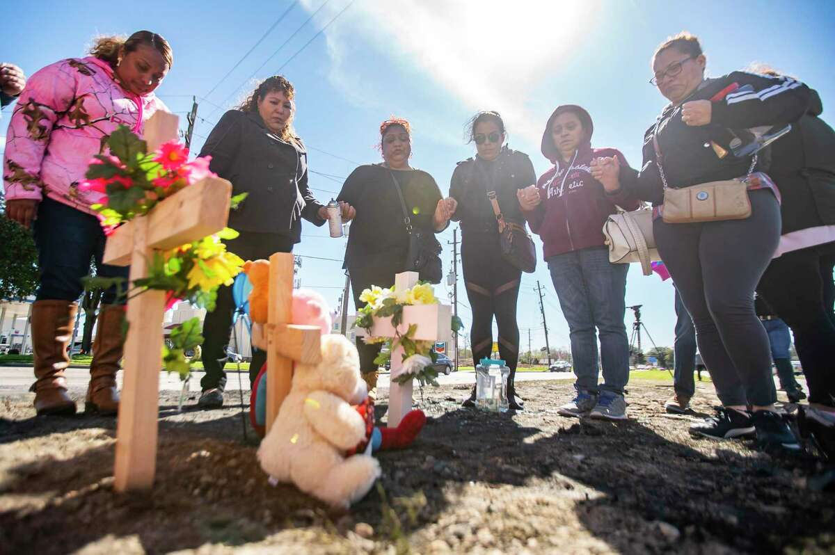 Friends pray Feb. 7, 2020, at a memorial they created at the site where Piedad Romero, her daughter Diana Soriano-Escobar and Diana's infant son Ricardo Escobar Jr. died in a crash at the intersection of Antoine and Beltway 8 in north Houston.