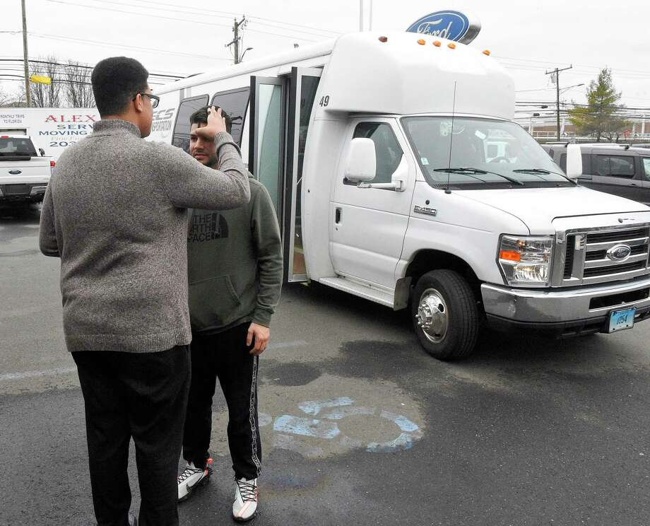 Luis Lavoura of Stamford receives ashes from Tyler Tarver, an Ambassador of Faith for St. Matthew's Church, during stop in Stamford, Conn. on Feb. 26, 2020 for the churches annual Ashes on the Move. As part of an out reach for the church, the church parish sends out the St. Matthew Bus onto the streets to offer people ashes on Ash Wednesday. It's about meeting people where they are , telling them about our great Catholic Church and to invite them in. Lavoura, a student at the University of St. Joseph, Connecticut, who recently moved to Stamford, went to the internet to find a local church offering Ashes and saw a posting about St. Matthews Ashes on the Move. He was one of a dozen people to receive ashes at the Stamford stopped outside of the Stamford Lincoln Ford dealership on McGee Avenue, one of twelve stops throughout Fairfield County. Photo: Matthew Brown / Hearst Connecticut Media / Stamford Advocate