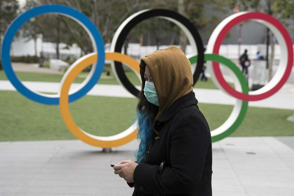 A woman wearing a face mask walks past the Olympic rings in front of the new National Stadium, the main stadium for the upcoming Tokyo 2020 Olympic and Paralympic Games.