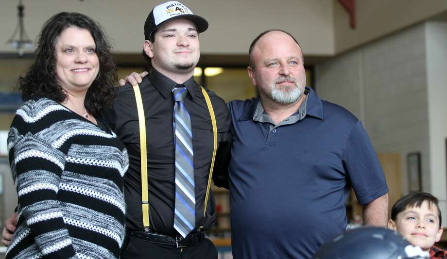 North Huron's Chris Augle poses with his family after signing his letter of intent on Wednesday morning. Photo: Eric Rutter/Huron Daily Tribune