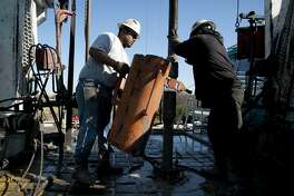 Toronto-based Trinidad Drilling Ltd. floorhands Julio Serrato, left, and Jaime Gonzalez work on the first drilling of the Reveille 1H Chesapeake Energy Corp. natural gas site in Fort Worth, Texas, U.S., on Monday, Nov. 23, 2009. Chesapeake Energy drills on much of the Barnett Shale over North Texas and Oklahoma. Photographer: Matt Nager/Bloomberg *** Local Caption *** Julio Serrato; Jaime Gonzalez