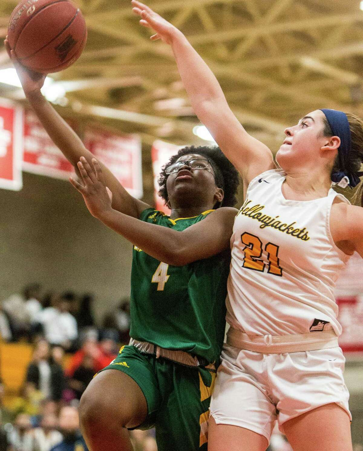 Hamden's Diamond White Goes up for a layup as East Haven's Isabella Ragaini goes for the block during the SCC championship game on Wednesday.