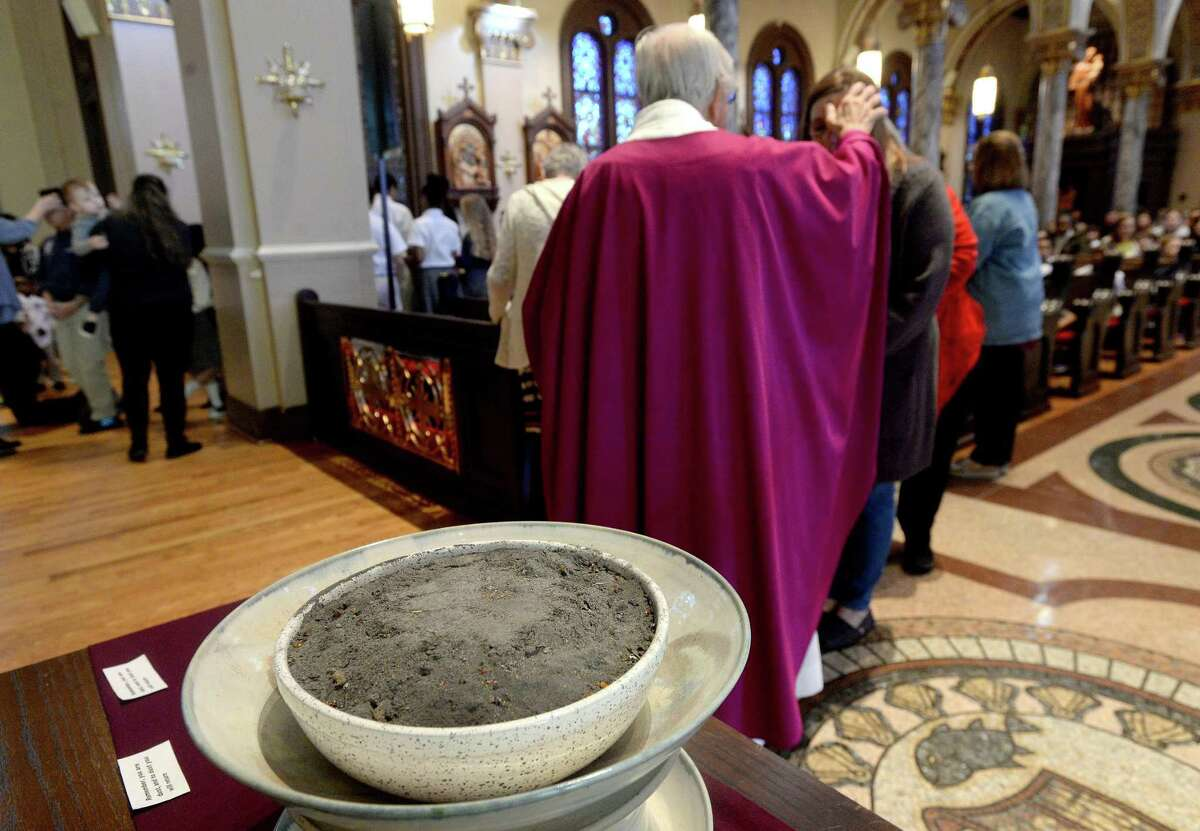 Msgr. Jack Dinkins distributes ashes during Ash Wednesday mass at St. Anthony Cathedral Basilica. Congregants and students from St. Anthony School filled the basilica for the early morning mass to begin the season of Lent. Photo taken Wednesday, February 26, 2020 Kim Brent/The Enterprise