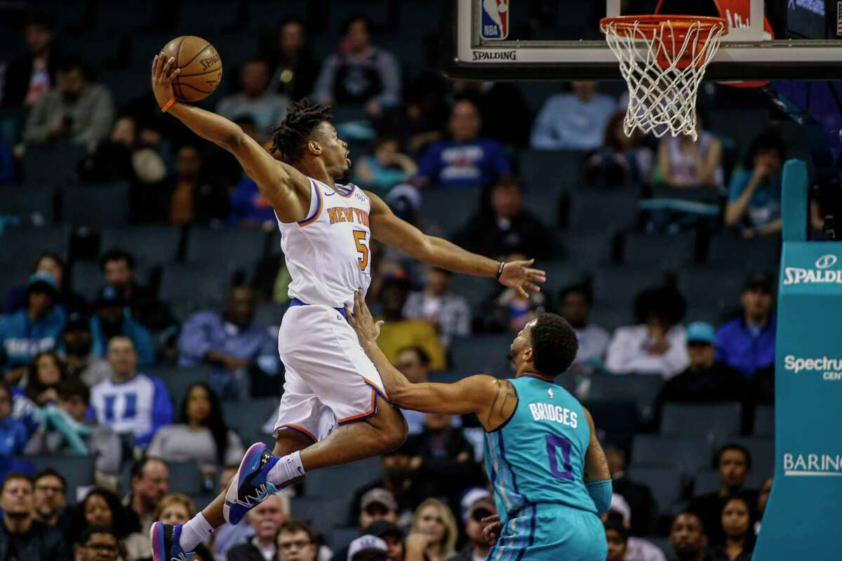 New York Knicks guard Dennis Smith Jr. drives for a dunk over Charlotte Hornets forward Miles Bridges during the first half of an NBA basketball game in Charlotte, N.C., Wednesday, Feb. 26, 2020. (AP Photo/Nell Redmond)