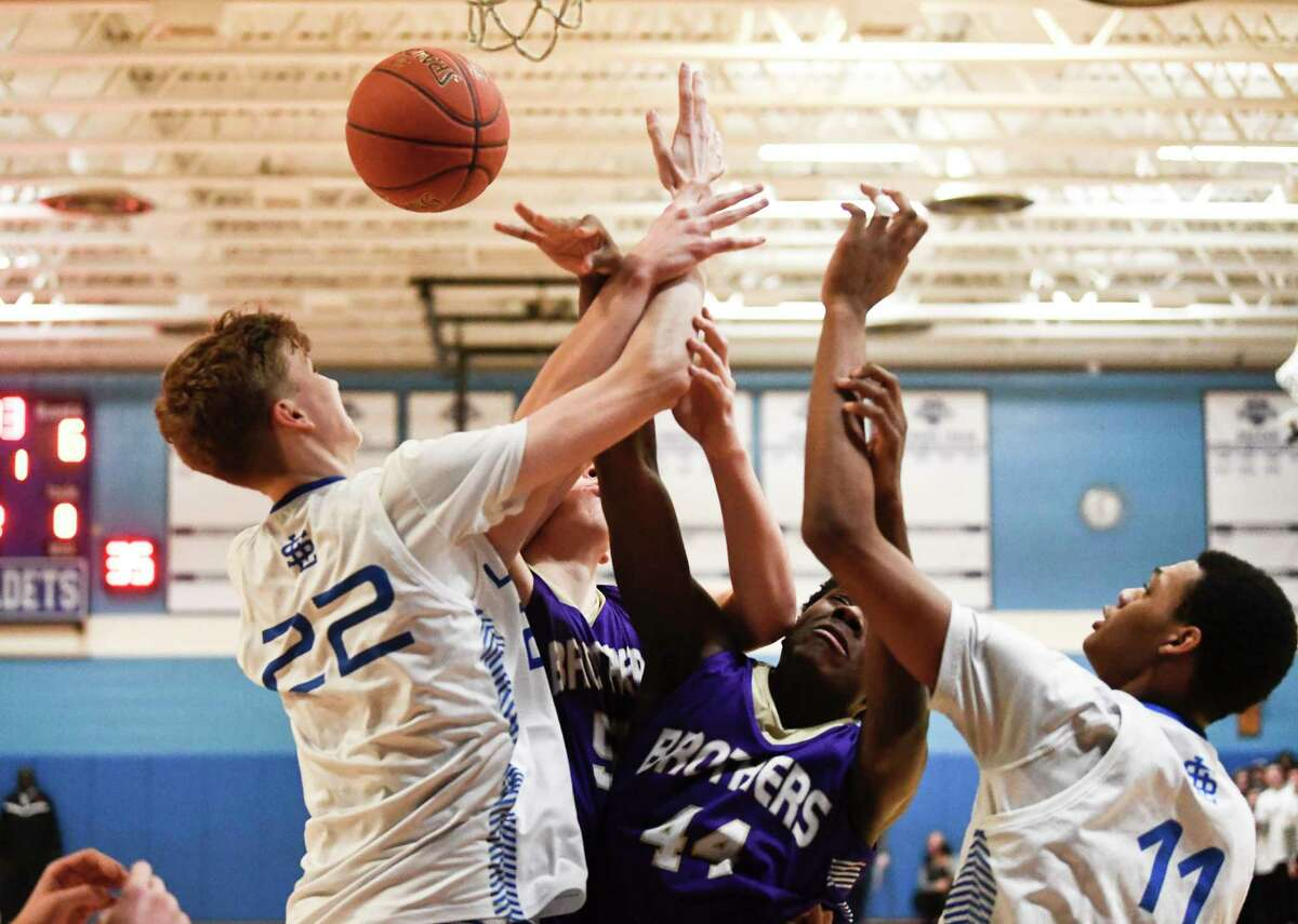 Albany County Executive Dan McCoy says the rate off coronavirus cases found during testing has dropped low enough for high-risk school sports to resume in the county. In this photograph, La Salle Institute and Christian Brothers Academy players battle for a rebound during the first half of a boys' Section II Class AA high school basketball game Wednesday, Feb. 26, 2020. (Hans Pennink / Special to the Times Union)
