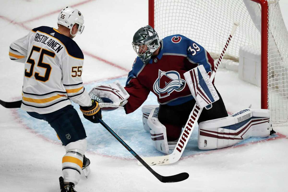 Colorado Avalanche goaltender Pavel Francouz, right, makes a glove save of a shot as Buffalo Sabres defenseman Rasmus Ristolainen looks on in the first period of an NHL hockey game Wednesday, Feb. 26, 2020, in Denver. (AP Photo/David Zalubowski)