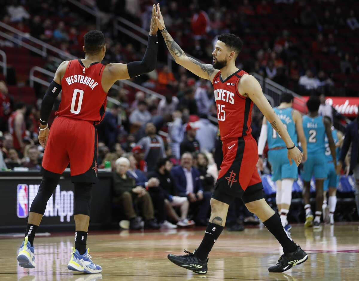 Houston Rockets guards Russell Westbrook (0) and Austin Rivers (25) high five during a break in the action against the Memphis Grizzlies during the second half of an NBA basketball game on Wednesday, Feb. 26, 2020, at Toyota Center in Houston.
