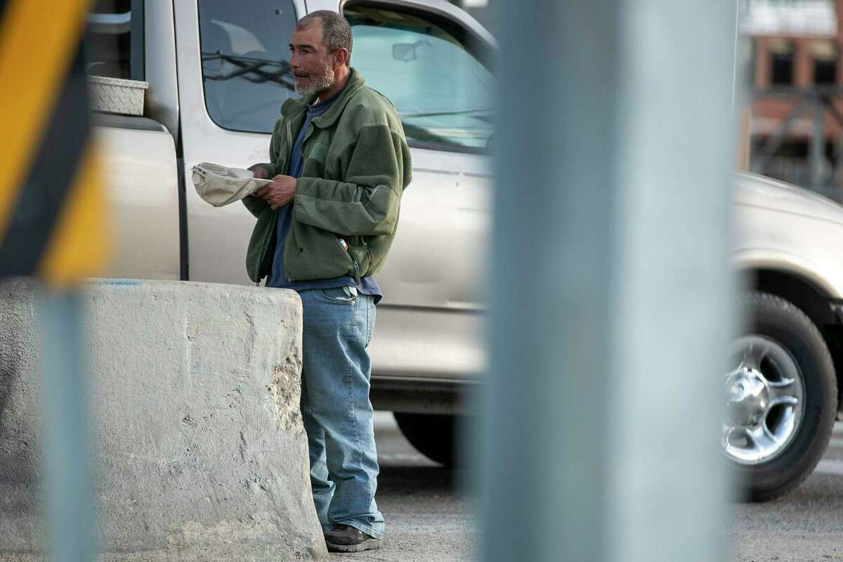 A man panhandles near the intersection of Brooklyn Avenue and East Elmira Street on Tuesday.