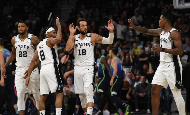 Marco Belinelli (18) of the San Antonio Spurs is congratulated by teammates Lonnie Walker IV, right, Rudy Gay (22) and Patty Mills (8) during second-half NBA action in the AT&T Center on Wednesday, Feb. 26, 2020.