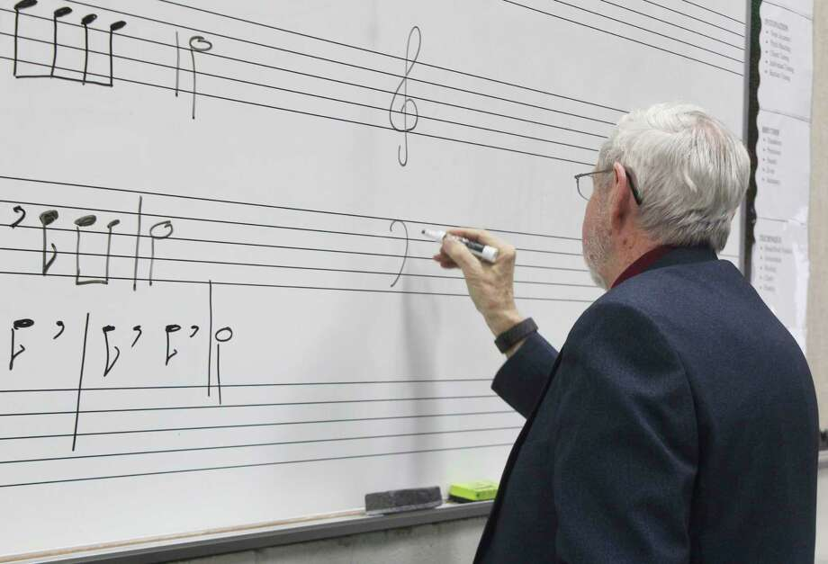 During class, Bass writes on the white board. He said he prefers to give students a visual aid during practice. (Star photo/Catherine Sweeney)