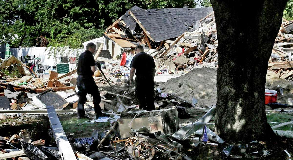 FILE - In this Sep. 21, 2018, file photo, fire investigators pause while searching the debris at a home which exploded following a gas line failure in Lawrence, Mass. The U.S. Attorney's office in Boston announced Wednesday, Feb. 26, 2020, that Columbia Gas Columbia agreed to plead guilty to violating the Pipeline Safety Act following an investigation into the catastrophic gas explosions. (AP Photo/Charles Krupa, File)