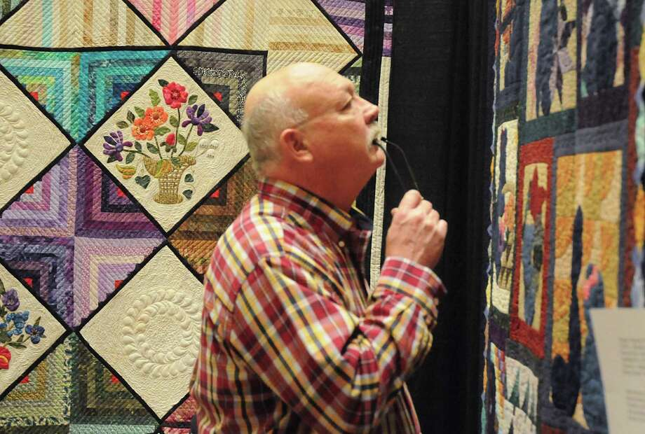 Quilter Bruce Lukowski, of Tomball, closely examines a quilt during the Tri-County Quilt Guild's Pieceful Moments Quilt Show at the Berry Center. Lukowski has been quilting for 10 years. Over 160 quilts were on display for the judging with entries from Waller, Montgomery, and northwest Harris County. David Hopper photograph Photo: David Hopper, Freelance / For The Chronicle / freelance