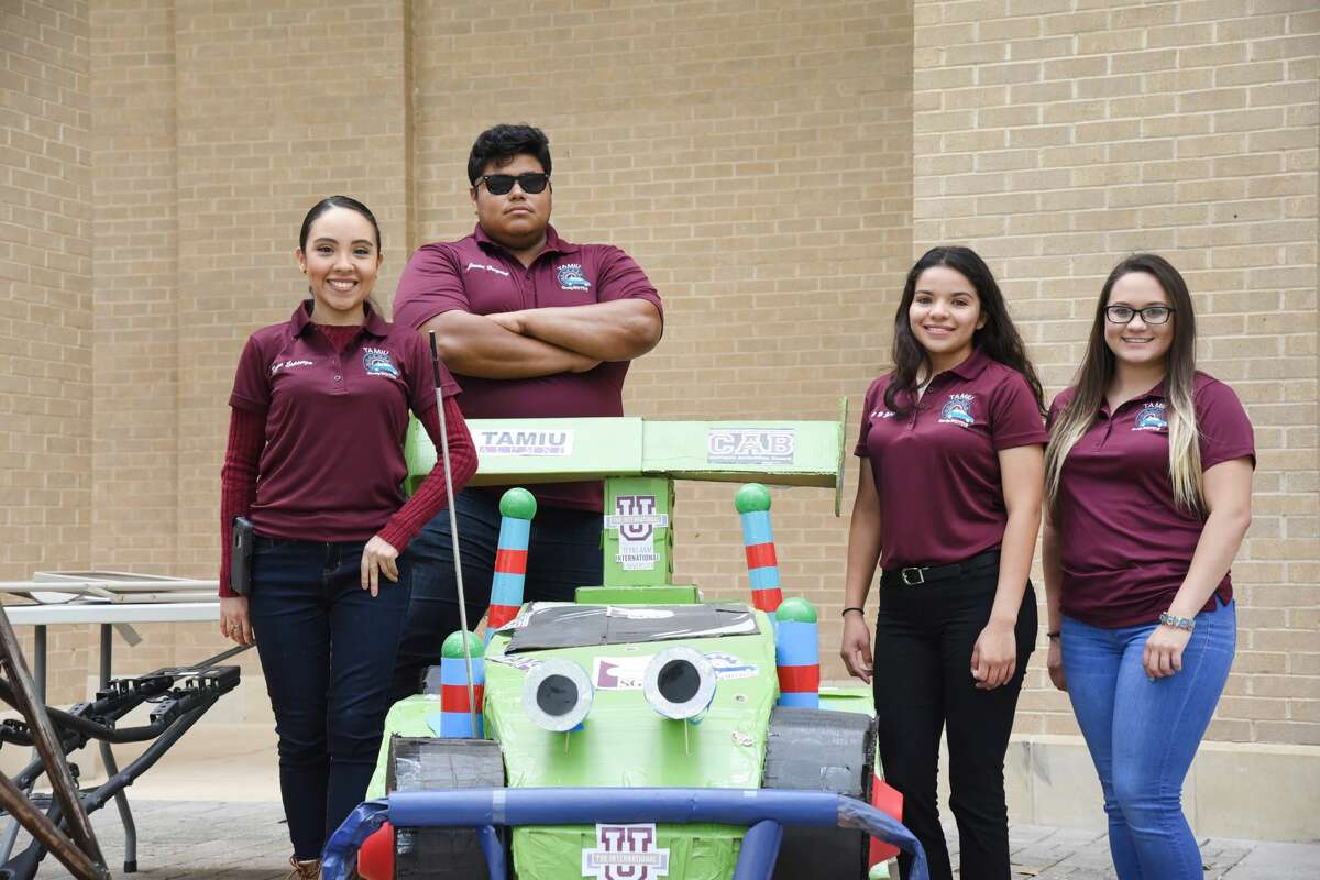 The Dusty Motors team stands next to a cardboard version of, Toy Story's RC during the Discover TAMIU Event at TAMIU, Saturday, April 7, 2018.