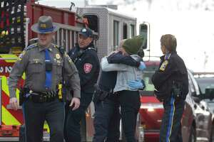 A woman who was detained after a substance, later determined to be Tylenol, fell from her pocket when she was entering the Superior Courthouse gets a hug from the State Trooper after she was released. Danbury, Conn, on Thursday, February 27, 2020.