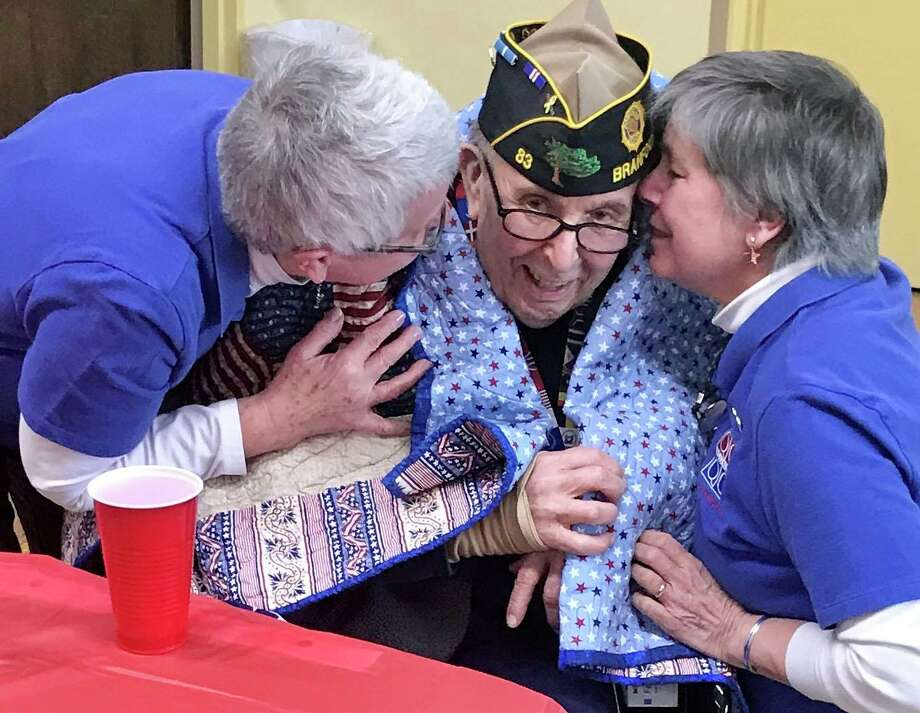 Korean War Army veteran John Migliaro accepting a quilt of valor from Jane Dougherty and Ann Marie Amman. Photo: Lisa Reisman / For Hearst Connecticut Media