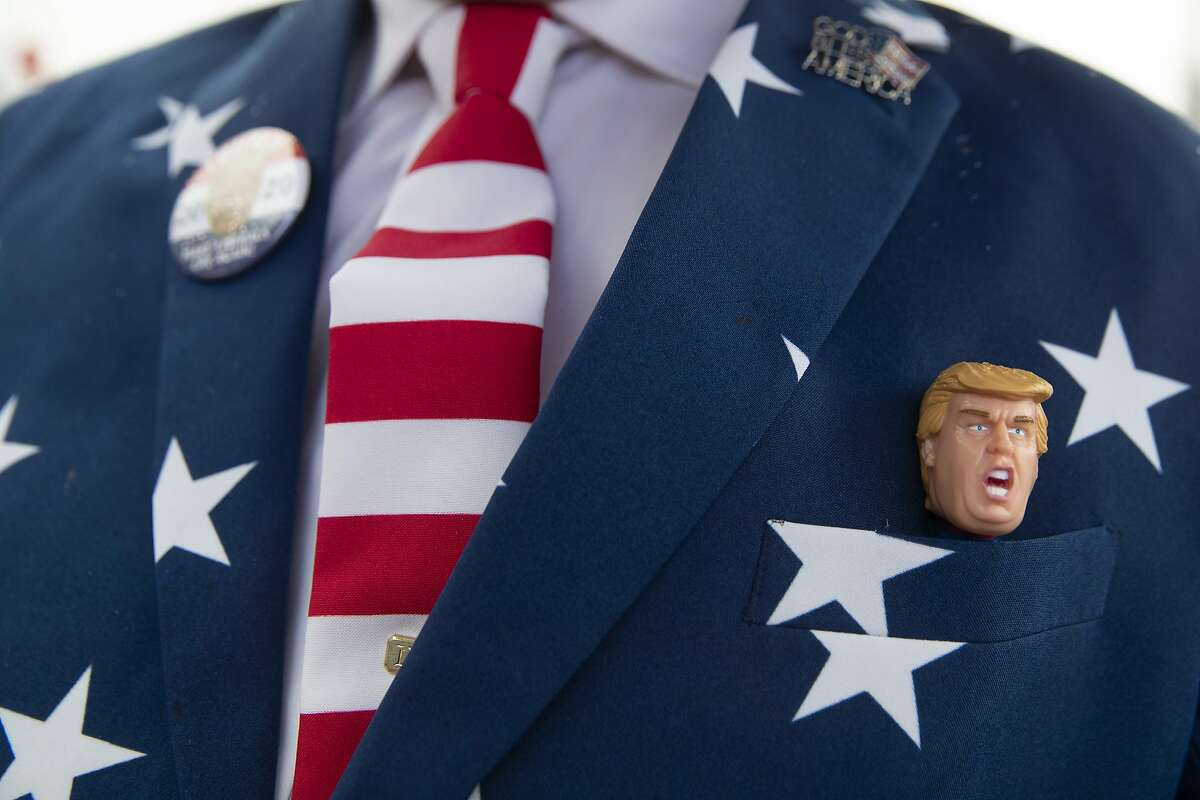 Richard Desrosiers, of Cape Cod, Mass., wears a suit and tie in the colors of the American Flag with and a figurine of President Donald Trump while waiting in line outside the venue where Trump will hold a campaign rally in the evening, Monday, Feb. 10, 2020, in Manchester, N.H. (AP Photo/Mary Altaffer)