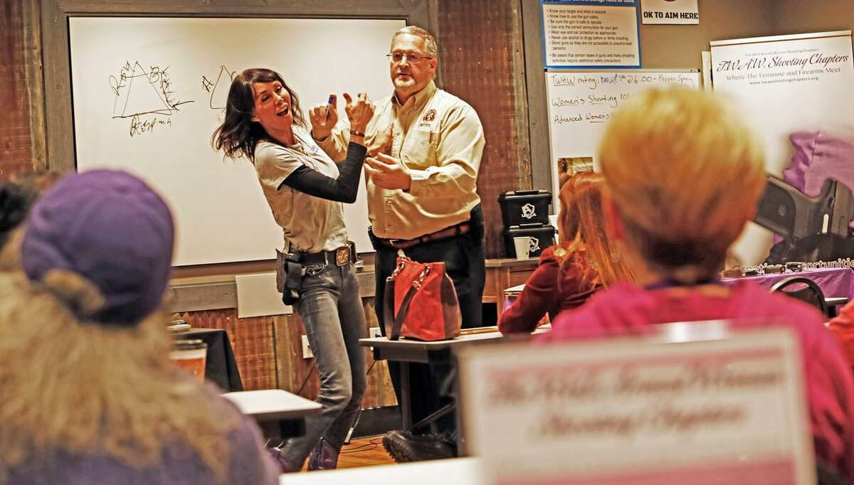 Holding a dummy canister, Ken Lewis demonstrates how to repel an attacker with pepper spray while Kari Grayson, founder of the San Antonio chapter of The Well Armed Woman, responds during a clinic at the monthly meeting of the club that focuses on firearms and self-defense.
