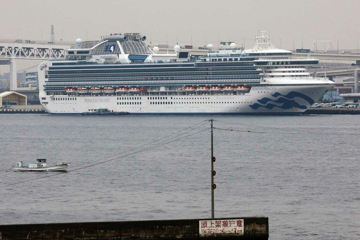 The Diamond Princess cruise ship is anchored at a port in Yokohama on Tuesday. Japanese health officials and experts on a government panel acknowledged that the quarantine of the virus-hit cruise ship was not perfect, but defended Japan's decision to release about 1,000 passengers after 14 days. (Kyodo News via AP)
