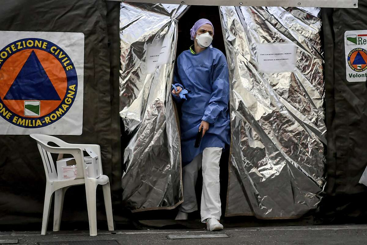 A paramedics wearing a mask gets out of a tent set up by the Italian Civil Protection outside the emergency ward of the Piacenza hospital, northern Italy, Thursday, Feb. 27, 2020. Italy is changing how it reports coronavirus cases and who will get tested in ways that could lower the country's caseload even as an outbreak centered in northern Italy spreads in Europe. (Claudio Furlan/Lapresse via AP)
