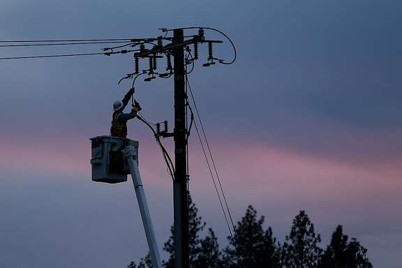 "FILE - In this Nov. 26, 2018, file photo, a Pacific Gas & Electric lineman works to repair a power line in fire-ravaged Paradise, Calif. PG&E has fired a contractor charged with hauling debris from the site of a deadly 2018 Northern California wildfire, saying the company was over-billing the utility and paying ""large sums of money and gifts"" to two utility supervisors. (AP Photo/Rich Pedroncelli, File)"