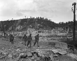 FILE - In this Aug. 9, 1944 file photo, U.S. soldiers walk by a bombed out cemetery in Agana, Guam. The 1941 Japanese invasion of Guam, which happened on the same December day as the attack on Hawaii's Pearl Harbor, set off years of forced labor, internment, torture, rape and beheadings.  Now, more than 75 years later, thousands of people on Guam, a U.S. territory, are expecting to get long-awaited compensation for their suffering at the hands of imperial Japan during World War II. (AP Photo/Joe Rosenthal, File)