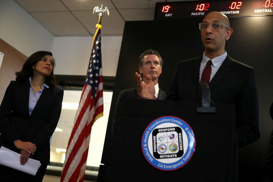 SACRAMENTO, CALIFORNIA - FEBRUARY 27: California Health and Human Services Agency Secretary Dr. Mark Ghaly (R) speaks speaks during a news conference as California Gov. Gavin Newsom (C) and California Department of Public Health Director and State Health Officer Dr. Sonia Angell (L) look on at the California Department of Public Health on February 27, 2020 in Sacramento, California. California Gov. Gavin Newsom joined State health officials to an update to the public about the state's response to the Coronavirus known as COVID-19 a day after a possible first case of person-to-person transmission was reported in Northern California. (Photo by Justin Sullivan/Getty Images)