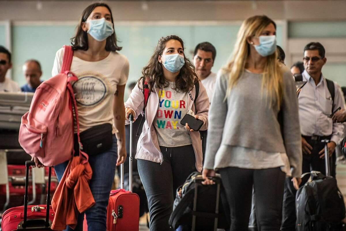 Passengers walk while wearing protective masks, as a preventive measure regarding the COVID-19 virus, at Jorge Chavez International Airport, in Lima on February 27, 2020. - So far, Peru has no record of the COVID-19 virus cases. (Photo by Ernesto BENAVIDES / AFP) (Photo by ERNESTO BENAVIDES/AFP via Getty Images)